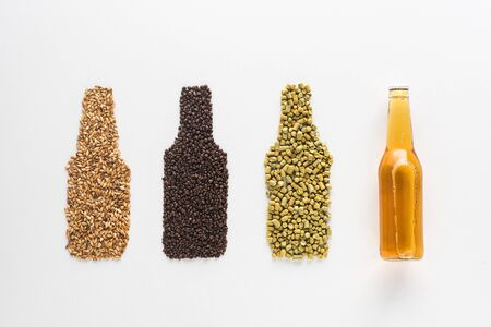 top view of bottle of light beer near wheat, coffee grains and pressed hop isolated on white