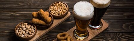 panoramic shot of glasses of dark and light beer near bowls with peanuts, pistachios, fried cheese and onion rings on wooden table