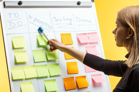 profile of businesswoman standing near white flipchart, pointing at words over sticky notes 免版税图像