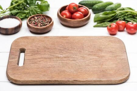 cutting board, cherry tomatoes, greenery, cucumbers, salt and spices