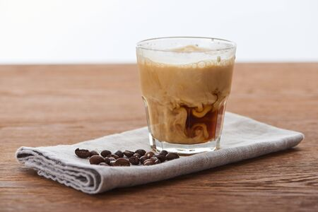 ice coffee mixing with milk in glass on napkin with coffee grains on wooden table isolated on white Stock Photo