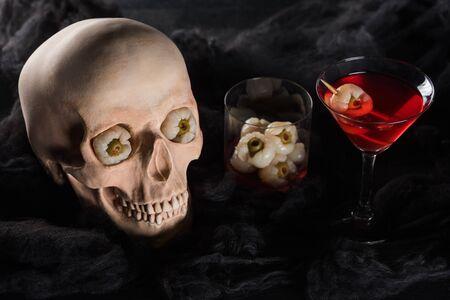 roter Cocktail in der Nähe von gruseligem Schädel auf schwarzem Hintergrund Standard-Bild