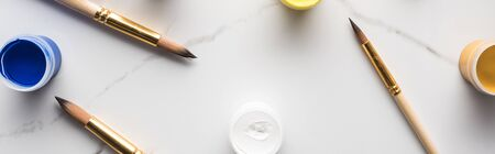 top view of colorful gouache paints and scattered paintbrushes on marble white surface, panoramic shot