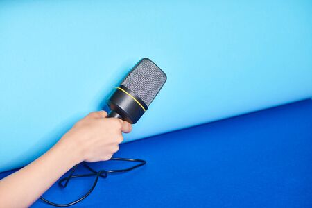 cropped view of woman holding microphone on turquoise background