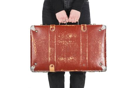 cropped view of woman in jeans holding vintage suitcase isolated on white