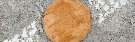 top view of coconut shavings near wooden board on grey textured background, panoramic shot Фото со стока