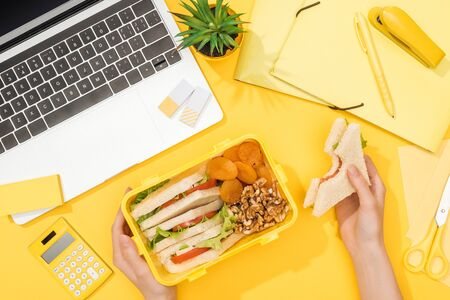 cropped view of woman holding sandwich in hand near lunch box, laptop and office supplies