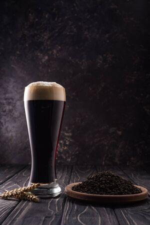 glass of dark beer near wheat spikes and plate with coffee grains on wooden table Фото со стока