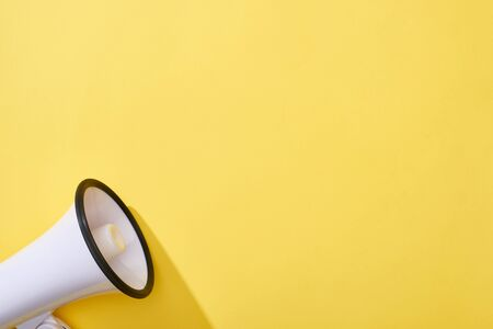 top view of loudspeaker on yellow background with copy space