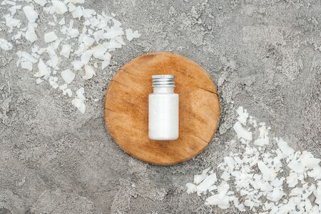 top view of coconut shavings near wooden board with coconut cream on grey textured background
