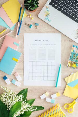 bovenaanzicht van maandelijkse planner, briefpapier, bloemen en laptop op houten tafel Stockfoto