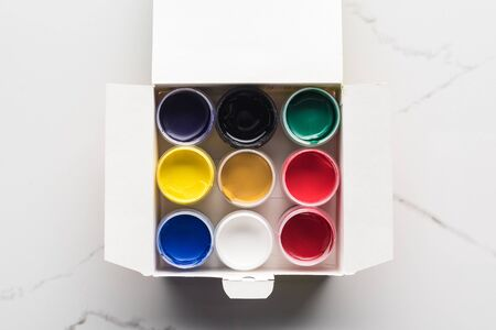 top view of colorful gouache paints in box on marble surface