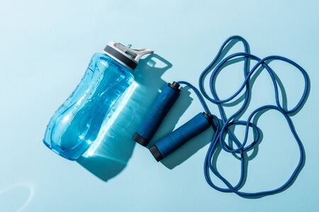 top view of sport bottle with water near skipping rope on blue Reklamní fotografie