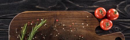 panoramic shot of wooden chopping board with spices, rosemary and cherry tomatoes