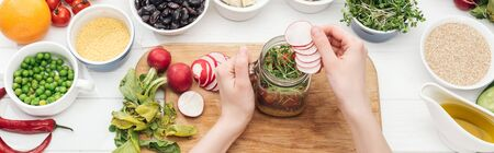 cropped view of woman adding radish slices in jar with salad on wooden white table, panoramic shot
