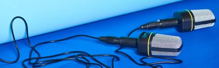 panoramic shot of black microphones with wires on colorful background 版權商用圖片 - 130301365