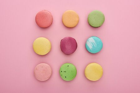 flat lay with delicious French macaroons on pink background