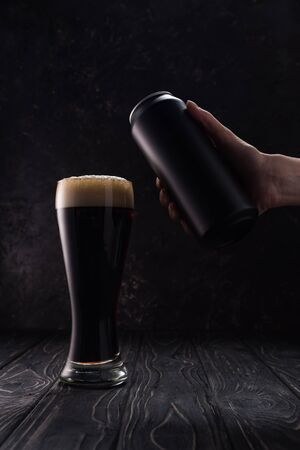 cropped view of man holding can near glass of dark beer with foam on wooden table