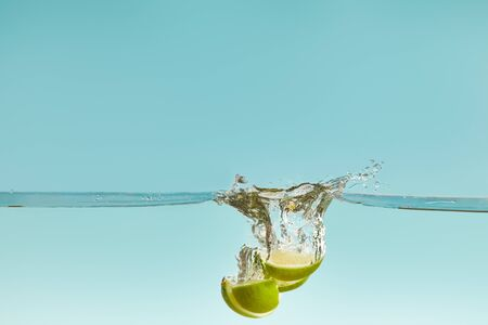 lime halves falling deep in water with splash on blue background