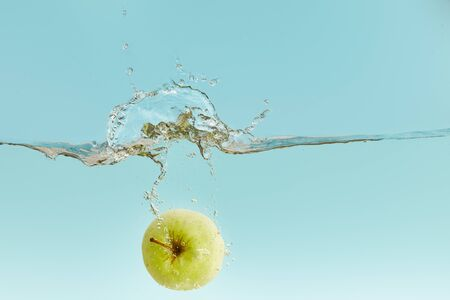 green apple falling deep in water with splash on blue background Stock Photo