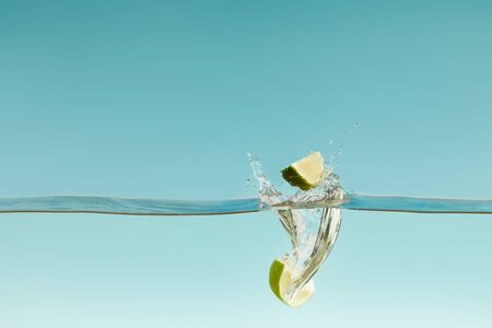 ripe lime halves falling deep in water with splashes on blue background Stock Photo