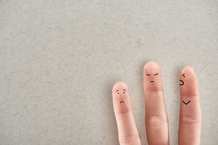partial view of man showing three fingers symbolizing aggressive abuser and sad victims on grey background Stockfoto