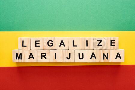top view of wooden blocks with legalize marijuana lettering on Rastafarian flag background