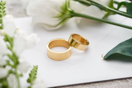 selective focus of wedding rings on white envelope near white eustoma flowers Foto de archivo