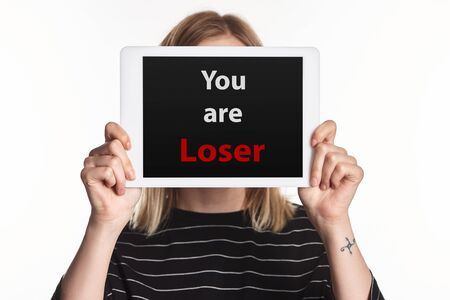 victim of cyberbullying showing digital tablet with you are loser lettering on screen isolated on white