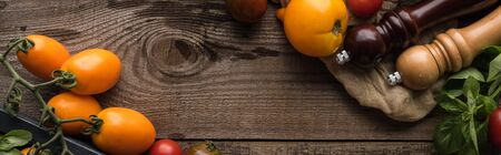 panoramic shot of tomatoes and spinach in box near pepper mill and salt mill on piece of fabric on wooden surface
