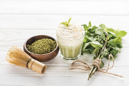 glass of matcha green tea with whipped cream on white table with powder, mint and whisk