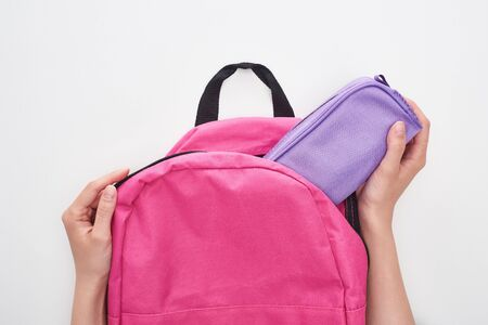 Partial view of schoolgirl taking violet pencil case from pink schoolbag isolated on white