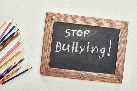 top view of chalkboard in wooden frame with stop bullying lettering near colored pencils on grey background Reklamní fotografie