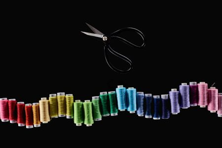 top view of bright and colorful threads and scissors isolated on black Stock Photo