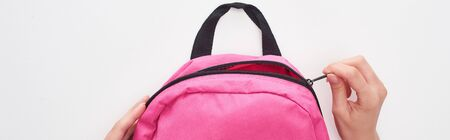Panoramic shot of schoolgirl zipping pink schoolbag isolated on white