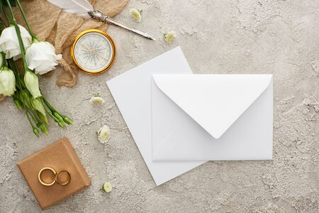 top view of white envelope, compass, wedding rings on gift box on grey textured surface Stockfoto