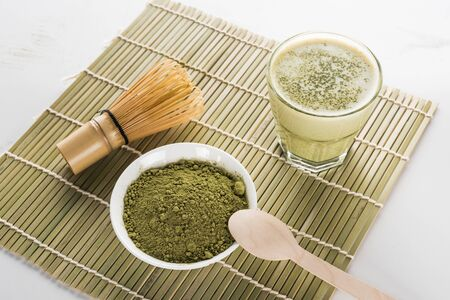 green matcha tea, whisk and spoon on bamboo mat