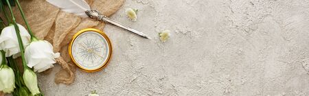 panoramic shot of quill pen on beige sackcloth near golden compass, scattered flowers and white eustoma flowers on grey textured surface