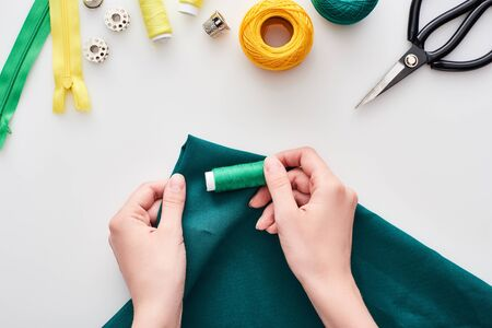 top view of seamstress holding colorful fabric and threads on white background