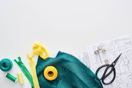 top view of zippers, scissors, thimbles, threads, knitting yarn balls, fabric and sewing patterns on white background Фото со стока