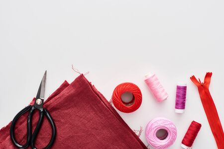 top view of colorful threads, knitting yarn balls, fabric, scissors and zipper on white background