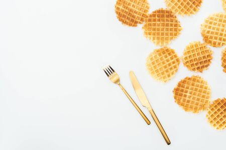 top view of scattered waffles and golden cutlery isolated on white