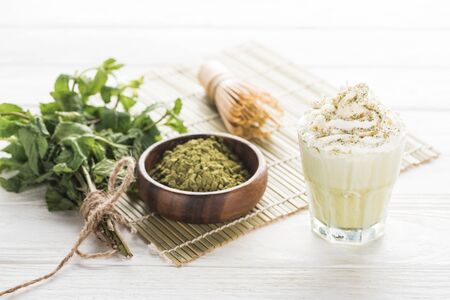 matcha tea with whipped cream on bamboo mat with powder, mint and whisk Reklamní fotografie