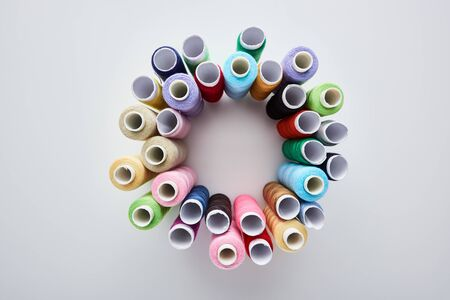 top view of bright and colorful threads on white background