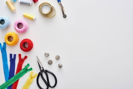 top view of zippers, scissors, thimbles, threads, knitting yarn balls, bobbins, tracing wheel, measuring tape on white background Фото со стока