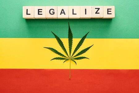 top view of cannabis leaf and wooden blocks with legalize lettering on Rastafarian flag background