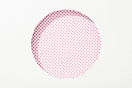 cut out round hole in white paper on pink and white dotted background Banque d'images - 130440337
