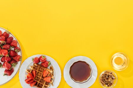 top view of plates with strawberries and waffles with cup of tea and bowl with nuts and honey on yellow Stockfoto