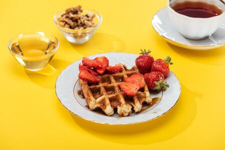 served breakfast with waffle and strawberries on plated, honey, nuts and tea on yellow background