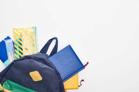Blue schoolbag with notepads, pencil case and school supplies isolated on white Stock Photo